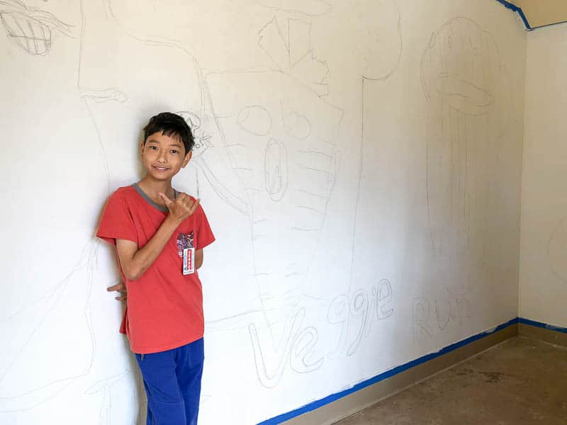 Student stands in front of mural wall showing sketch of design
