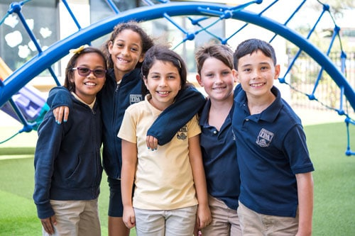 Five elementary students standing together smiling