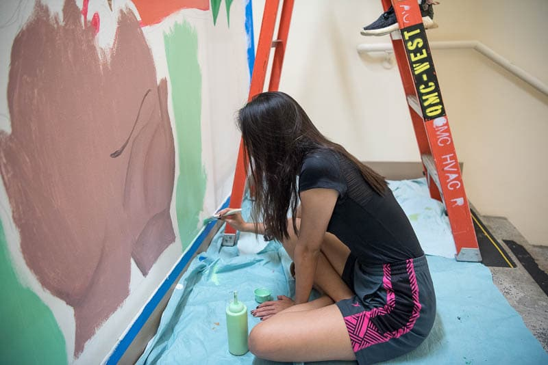 Student sitting on the floor painting mural on wall