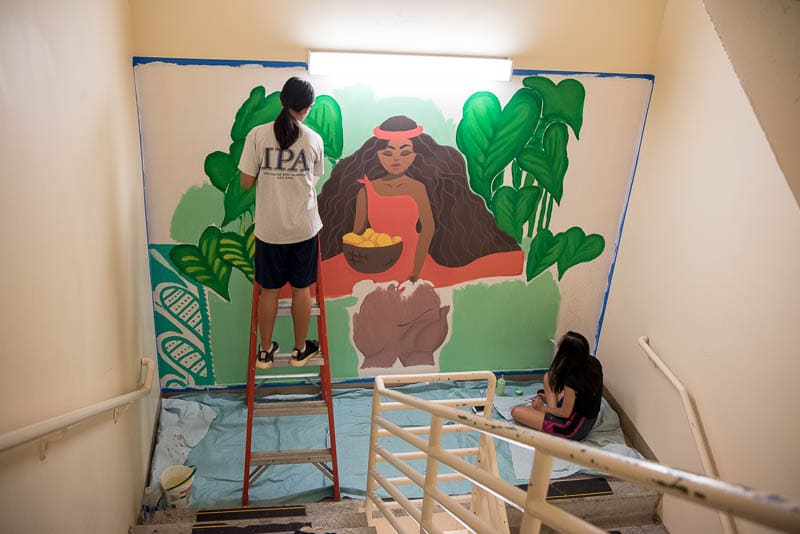 Students painting a mural in hospital stairwell