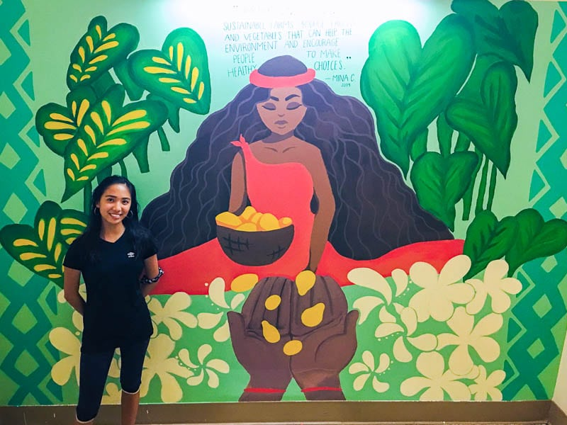 Student stands in front of her completed mural