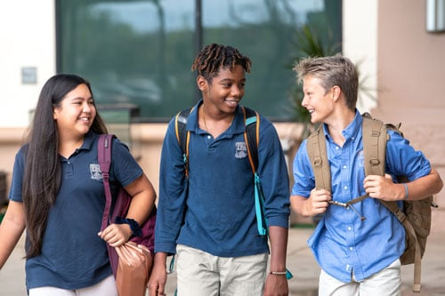 Three middle school students walking together talking
