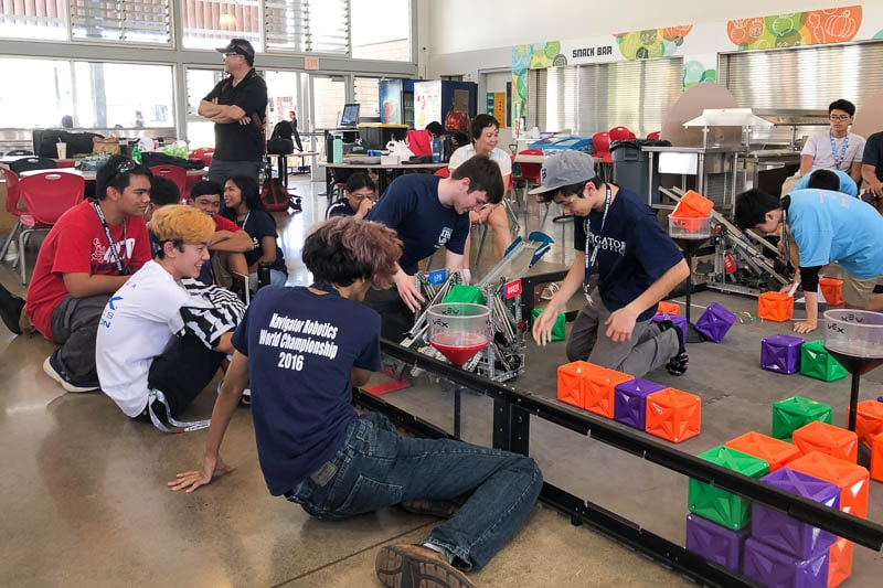 Students sitting around competition field at robotics tournament.