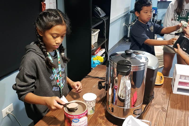 Student making hot cocoa in the Navigator Credit Union cafe