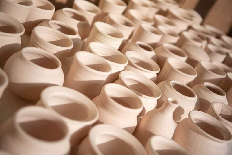 Table full of unglazed ceramic pots