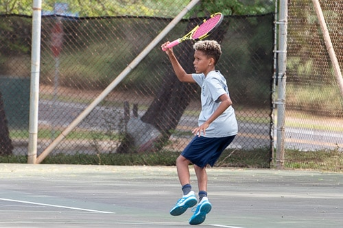 Boys tennis player hitting ball
