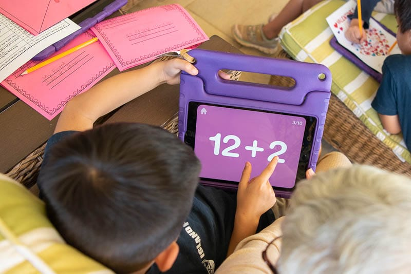 Student and senior do math on an iPad