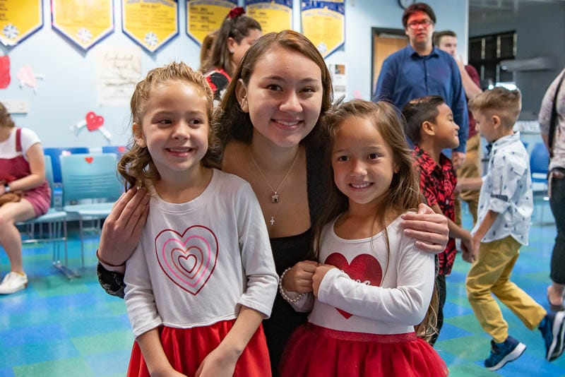Senior student with kindergarteners at Valentine's dance