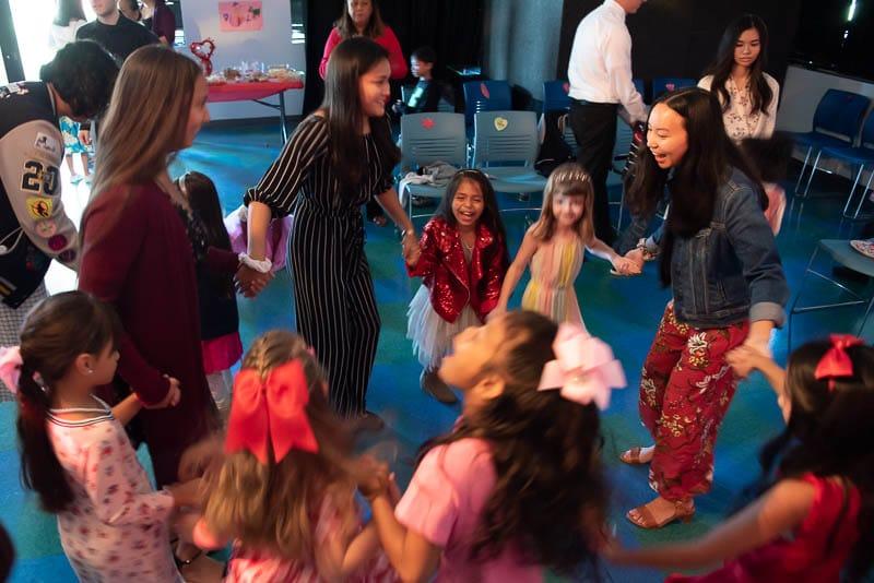 Seniors and kindergarteners dancing in a circle