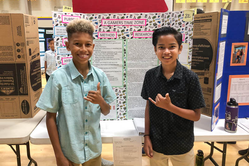 iddle school students standing in front of science fair project
