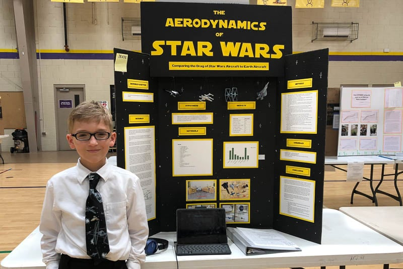 iddle school student standing in front of science fair project