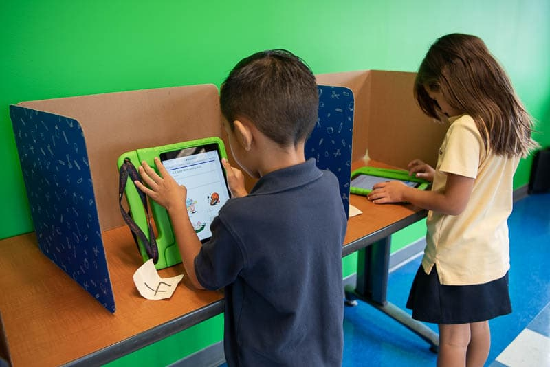 Grade 1 students voting in voting booths