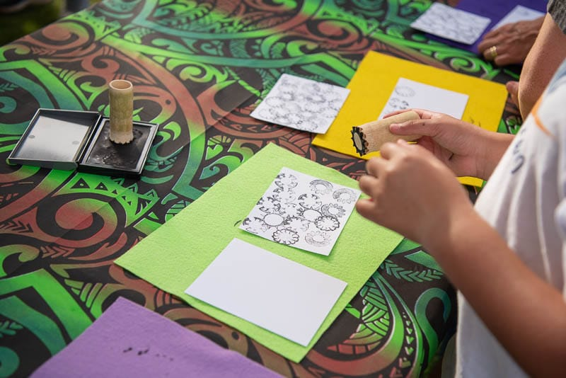 Students using stamps carved from bamboo to decorate paper