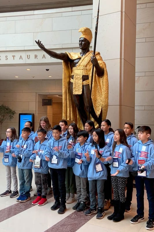 Grade 5 students chanting the IPA oli in front of Kamehameha I at the National Statuary Hall