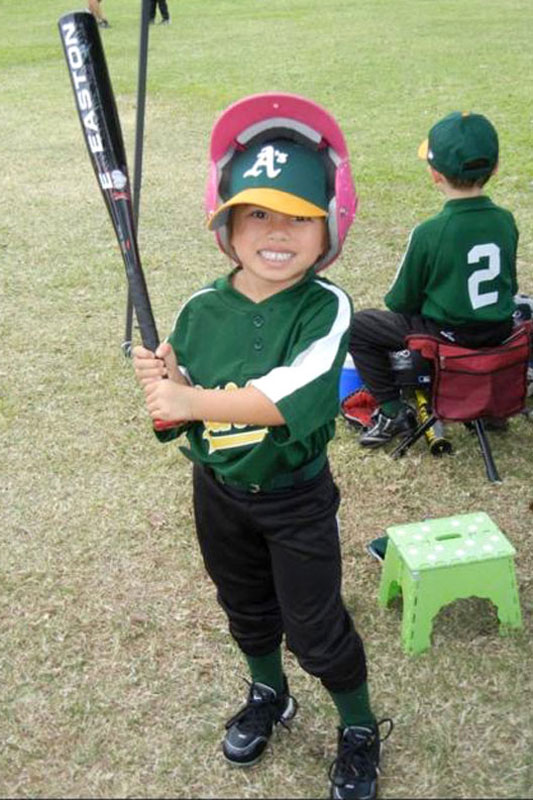 Four year old girl in baseball uniform