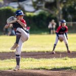 Middle school female baseball pitcher winding up