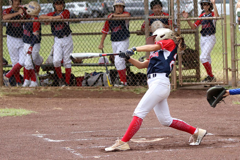 Middle school female baseball player at bat