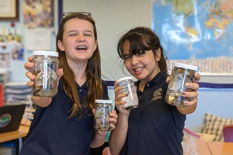 Girls holding up donation jars