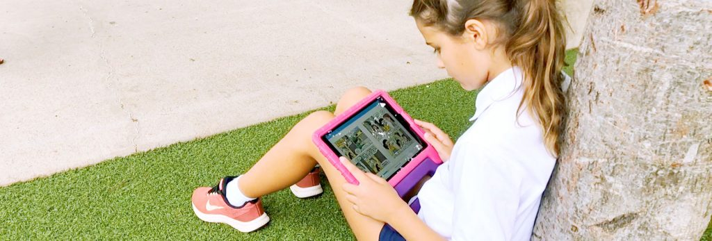 Student sitting outside against a tree reading on a iPad
