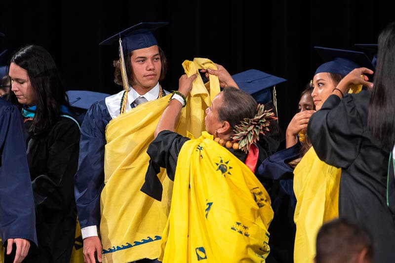Ms. Momi ties a kihei on Nalu Paz '19 at the IPA commencement ceremony. Ms. Momi was his kindergarten teacher.