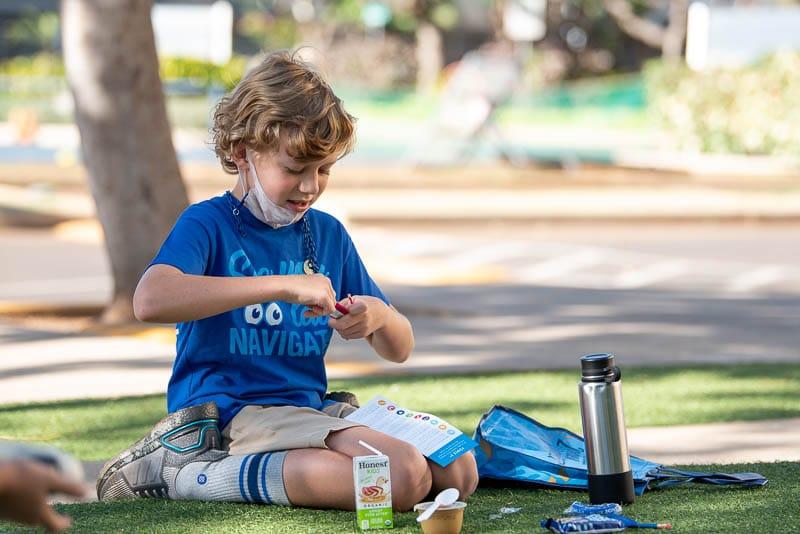 Student enjoying snack on grass