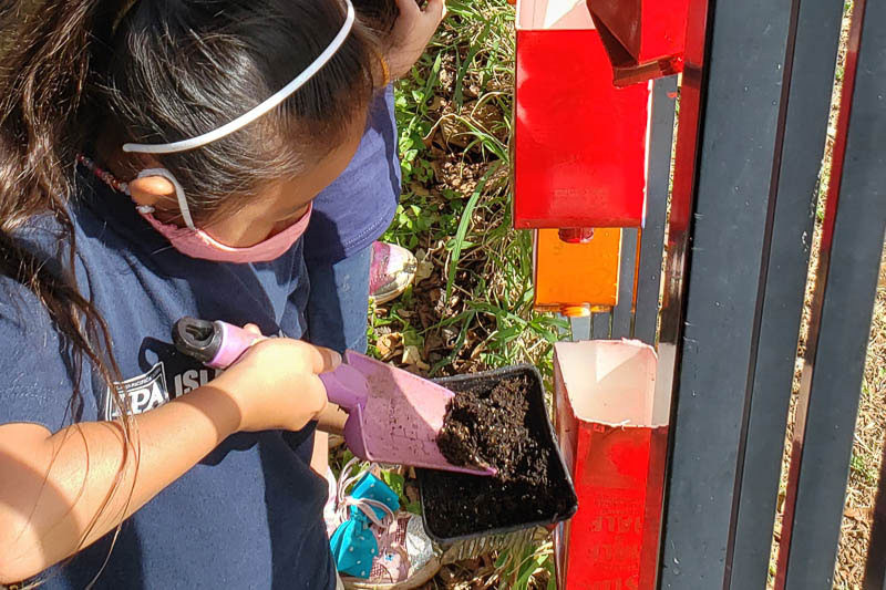Students filling container garden with soil