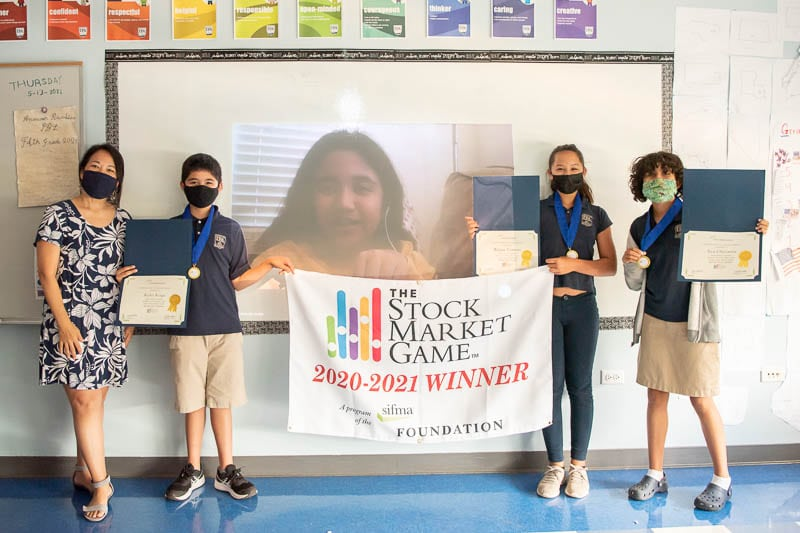 Grade 5 students with awards from The Stock Market Game competition.