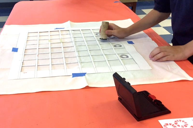 Student stamping design on konane board