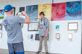 Student poses for photo in art gallery.