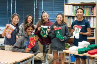 Students holding up handmade holiday stockings.