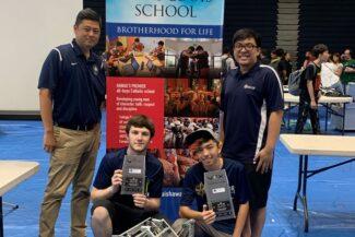 IPA Navigator Robotics team members and coach pose with tournament awards and robots