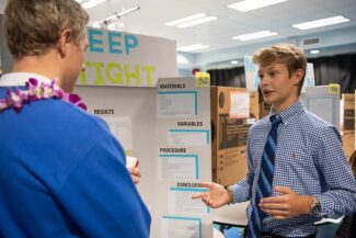 Student standing in front of science fair project talking to judge.