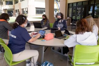 Students around table working on art project.